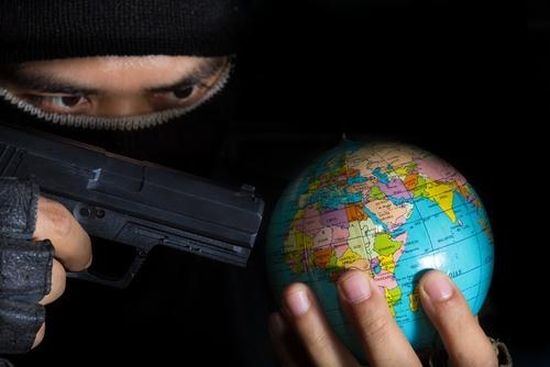man holding a gun at a globe