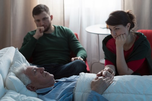 young man and woman sitting in hospital room worried about older man who is lying in the hospital bed