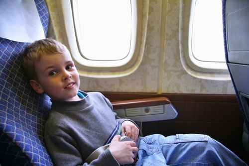 young boy sitting in airplane window seat