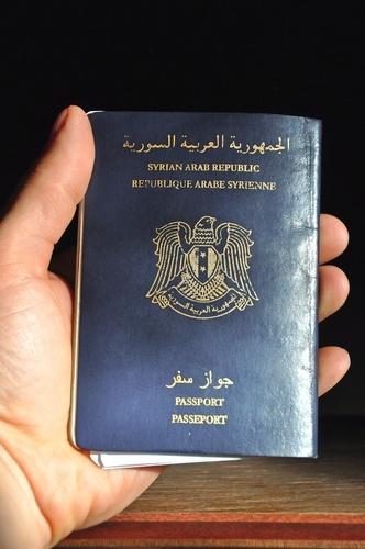 man's hand holding Syrian passport