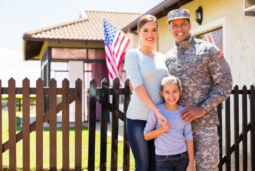male soldier standing with his wife and child outside house displaying the U.S. flag