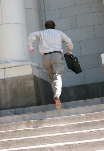 man with briefcase running up steps to courthouse