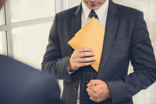man placing envelope in his suit as an example of embezzlement in California