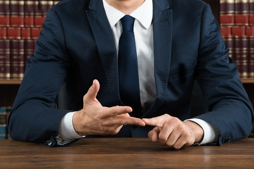 close-up of male lawyer ticking off reasons on his fingers