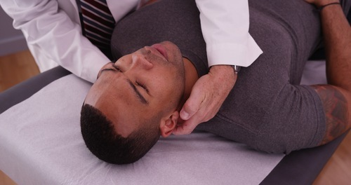 chiropractor adjusting head and neck of male patient