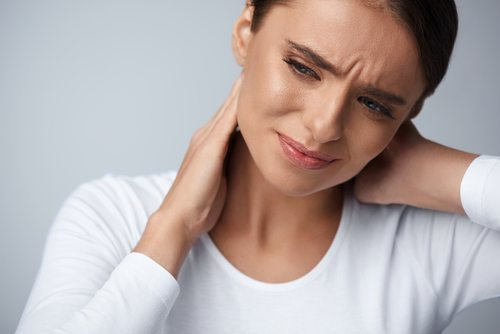 attractive young woman holding neck and grimacing in pain