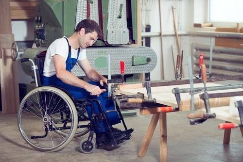 young man in wheelchair sitting in carpentry workshop