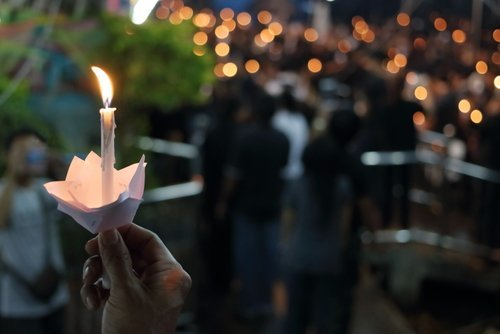 Mourners at a funeral holding candles - families may be able to sue when a loved one suffers a wrongful death.