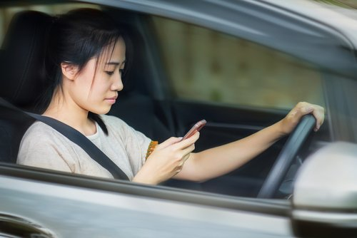 Woman texting while behind the wheel. Since this is intentional behavior, it qualifies as gross negligence if it causes an accident.