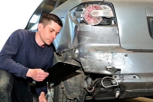 insurance adjuster examining car in body shop