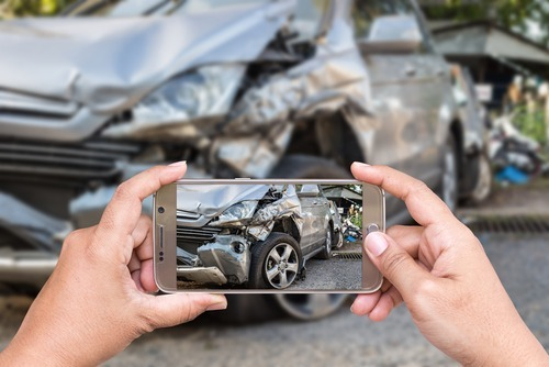 close up of someone taking photos of a bad car wreck on his phone