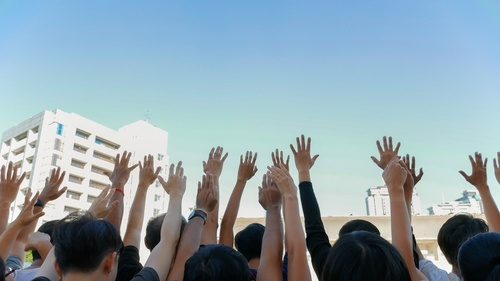 group of people raising hands outside multistory building