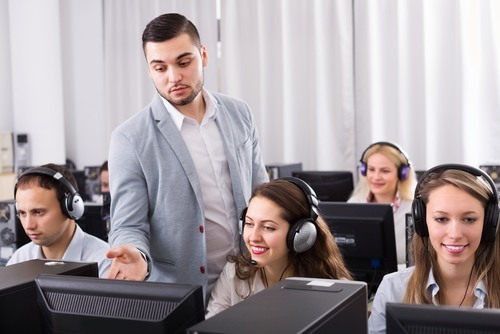 male boss in suit supervising receptionists in headsets