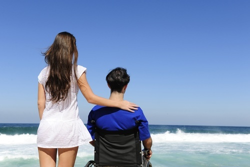 rear shot of young couple on beach with man in wheelchair