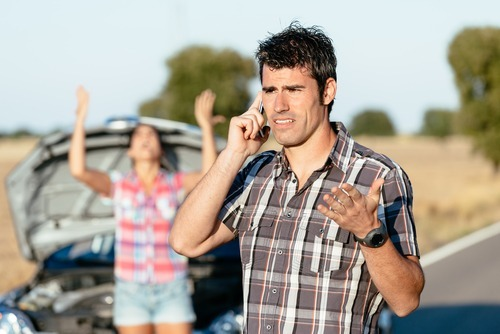 man on phone after car accident while angry woman in background is yelling at him
