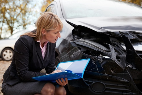 female insurance adjuster inspecting damaged car