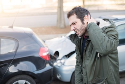man holding the back of his head in front of two cars that have collided