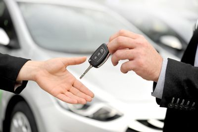Close up of person handing car key to someone else