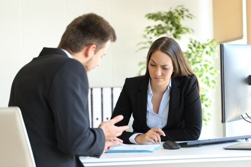 man and women in suit across table from each other negotiating