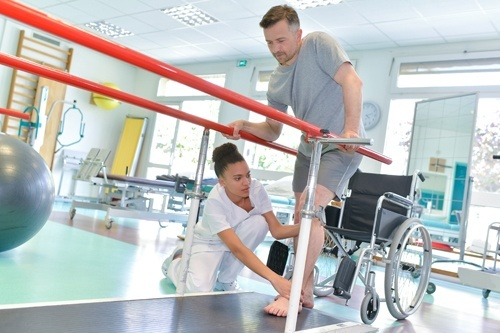 occupational therapist helping man with wheelchair learn to walk again