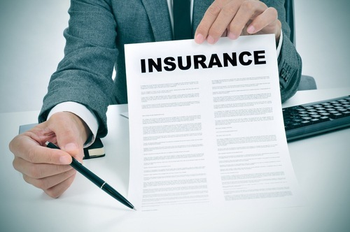 "man in suit holding up pen and paper with the title ""Insurance"""