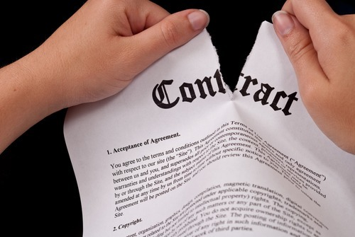 "close up on hands ripping a piece of paper titled ""Contract"""
