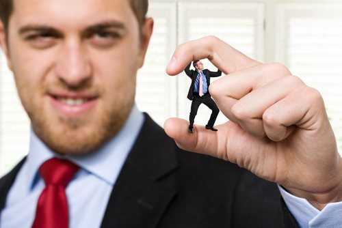 big man in suit squishing little man in suit in between his thumb and forefinger