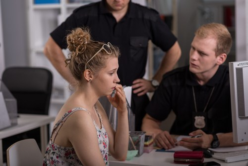 young woman making report to young policeman