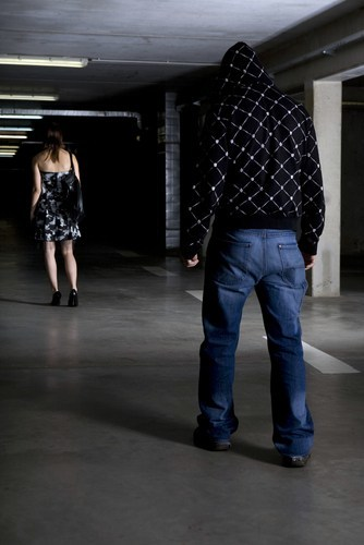 man stalking dressed up woman in a parking garage