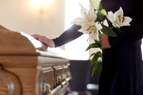 woman holding bunch of lilies next to casket