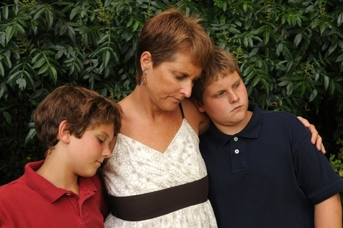 grieving woman with her two young sons