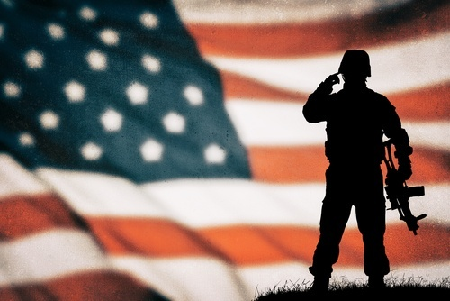 Silhouette of soldier in combat gear standing in front of American flag