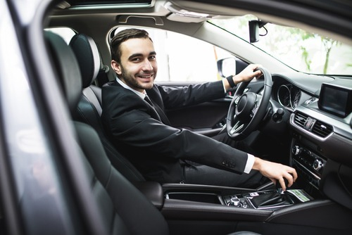 young man in suit behind wheel of vehicle with welcoming expression