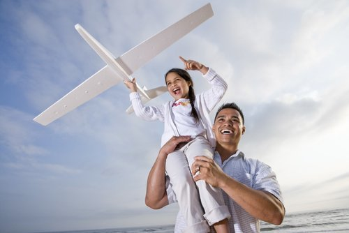 father holding up his young daughter who has a model airplane in his hand