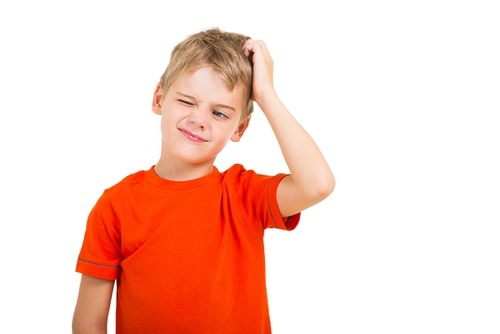 young boy scratching his head and scrunching his face in confusion