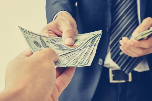 man in business suit handing cash to someone