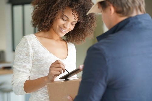 Woman signing for a package from a delivery man