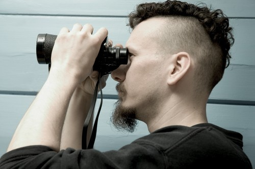 bearded man looking through binoculars outside of house