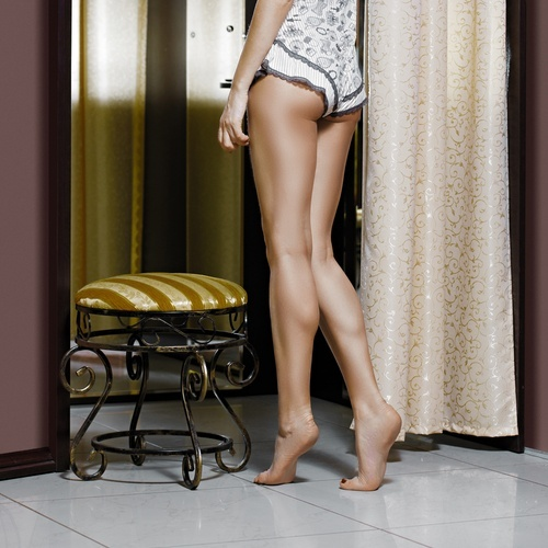 scantily clad woman on her toes in dressing room