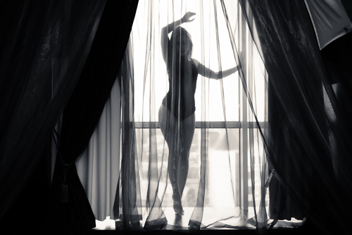 scantily clad woman posing behind sheer curtain