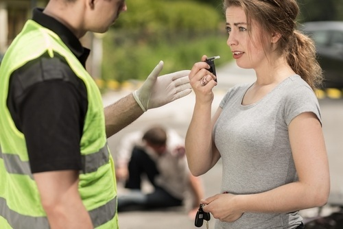 Police administering breath test to DUI suspect