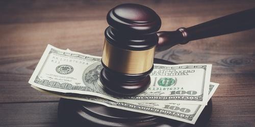 judge's gavel on top of two hundred-dollar bills