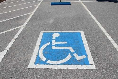 Handicapped parking space marked with wheelchair symbol and adjacent crosshatched wheelchair access area.