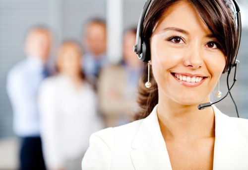 female receptionist with headset in front of blurred images of four business people