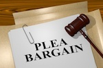 plea bargain printed on paper with gavel