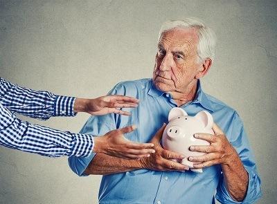 Old man holding a piggy bank
