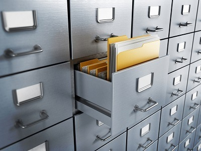 An open filing cabinet with documents showing