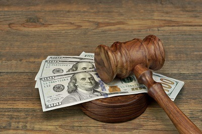 Gavel laying on 100 dollar bills