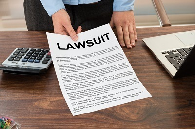 Man holding paper labeled lawsuit