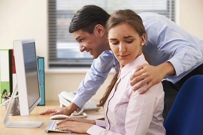 Man with hand on woman's shoulder representing workplace harassment